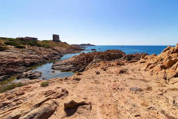 Foto de paisagem de uma praia com grandes pedras na colina em um céu azul claro