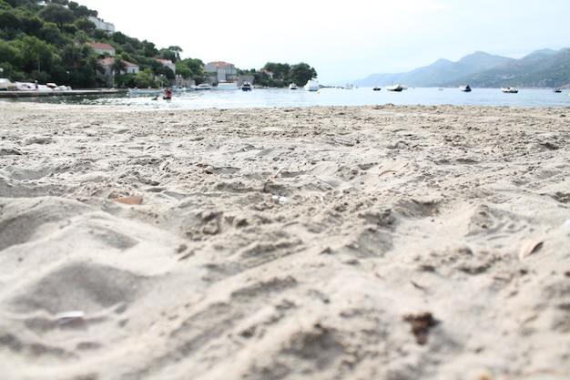 Foto de paisagem de uma praia de areia com céu azul claro