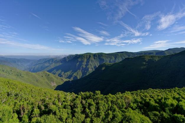 Foto de paisagem distante de colinas e montanhas verdes sob um céu ensolarado