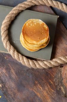 Foto de panquecas deliciosas com cordas na mesa de madeira com comida no café da manhã
