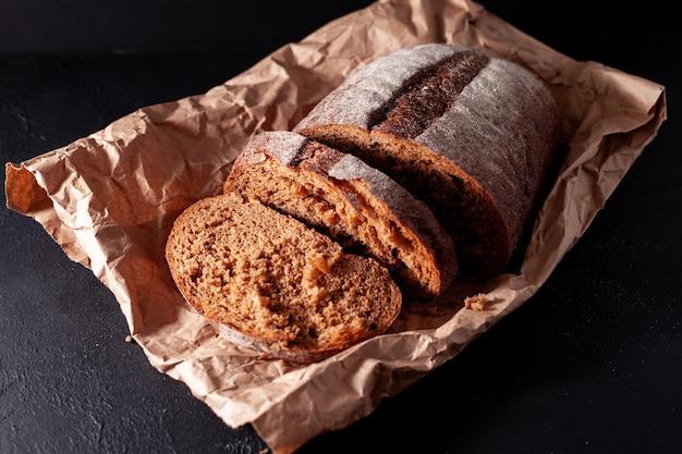 Foto de pão em uma sacola artesanal o pacote está sobre uma superfície de concreto escuro