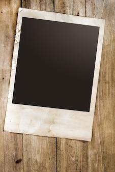Foto de papel vazia dos instans da câmera polaroid na mesa de madeira - estilo vintage e retro