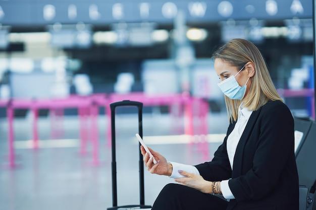 Foto de passageira adulta usando smartphone no aeroporto