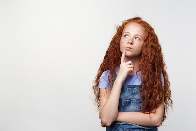Foto de pensar sardas fofas garotinha com cabelo ruivo, parece séria e duvida, toca o queixo, desvia o olhar sobre fundo branco com espaço de cópia no lado esquerdo.