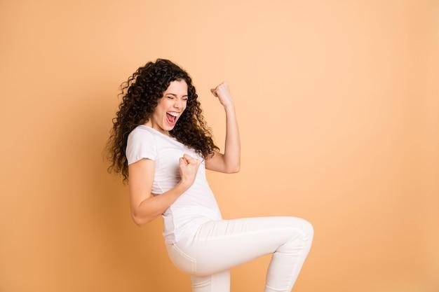 Foto de perfil da incrível senhora gritando triunfando levantando os punhos preços de venda de compras começando a usar roupas casuais brancas com fundo bege