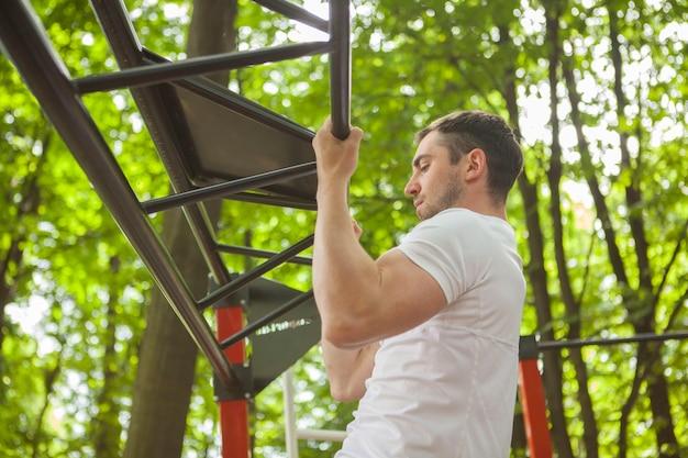 Foto de perfil de baixo ângulo de um esportista fazendo flexões ao ar livre