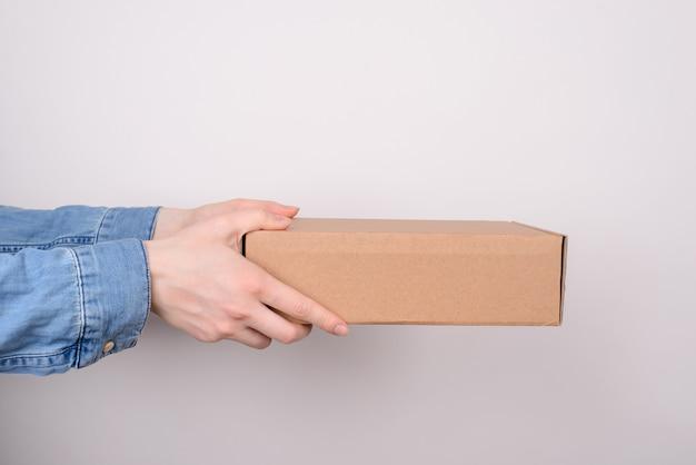 Foto de perfil de braços segurando uma caixa de papelão isolada