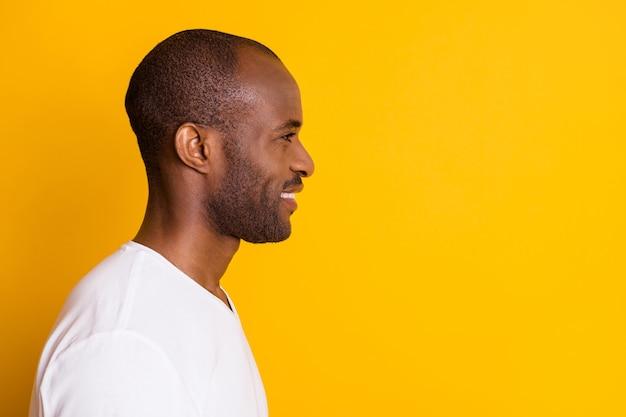 Foto de perfil de close up de cara de pele morena alegre e atraente, bom humor, sorriso radiante, olhar espaço vazio, usar camiseta branca casual isolada fundo de cor amarela brilhante vívida