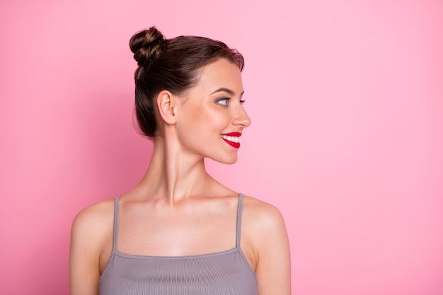 Foto de perfil de close up de uma garota incrível, pãezinhos engraçados, pomada vermelha olhando o espaço vazio, usar uma blusa cinza de verão casual isolada cor rosa pastel