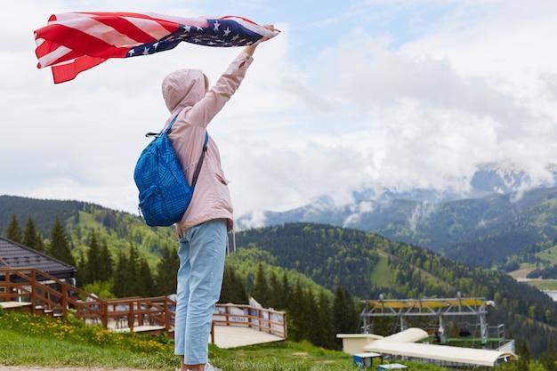 Foto de perfil de comprimento total de mulher jovem e bonita com bandeira americana realizada na mão estendida em pé na frente da base turística