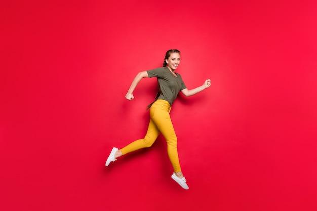 Foto de perfil de corpo inteiro de senhora ativa pulando de alta competição participante da maratona correndo rápido desgaste calça amarela casual camiseta verde isolado fundo de cor vermelha