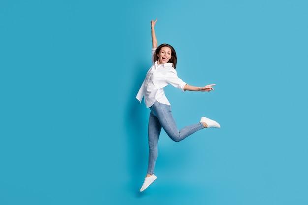 Foto de perfil de corpo inteiro de senhora bonita atraente aparência charmosa pulando alto regozijando-se bom dia bom humor rua olhar usar camisa branca jeans sapatos isolados de cor azul de fundo
