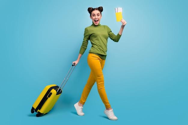 Foto de perfil de corpo inteiro de senhora bonita engraçada segurar bilhetes passaporte voo barato mala com rodinhas caminhada aeroporto usar gola verde calça amarela calça calça azul isolada parede