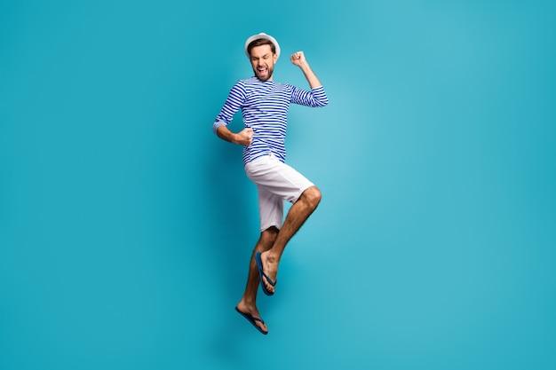 Foto de perfil de corpo inteiro de um cara atônito turista pular alto comemorando férias começar vestir camisa listrada de marinheiro boné shorts flip-flops isolado cor azul