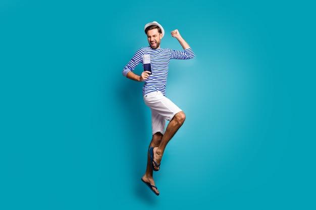 Foto de perfil de corpo inteiro de um cara funky turista pulando alto comemorando férias começar a obter visto usar camiseta listrada de marinheiro colete boné shorts chinelos isolados cor azul