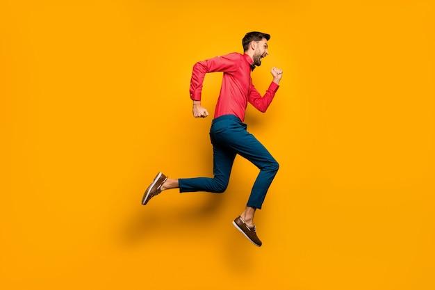 Foto de perfil de corpo inteiro de um cara louco e engraçado pulando alto correndo atrás de compras pretas na sexta-feira. usar camisa vermelha na moda e calça de gravata borboleta.