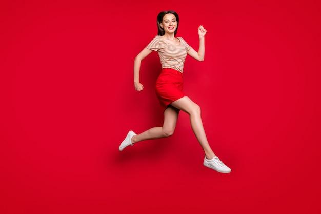 Foto de perfil de corpo inteiro de uma moça bonita pulando alto correndo rápido