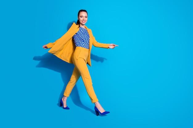 Foto de perfil de corpo inteiro de uma senhora atraente trabalhadora caminhando em uma conferência corporativa usar blazer amarelo calças de terno blazer pontilhado calçado de salto alto isolado fundo de cor azul brilhante