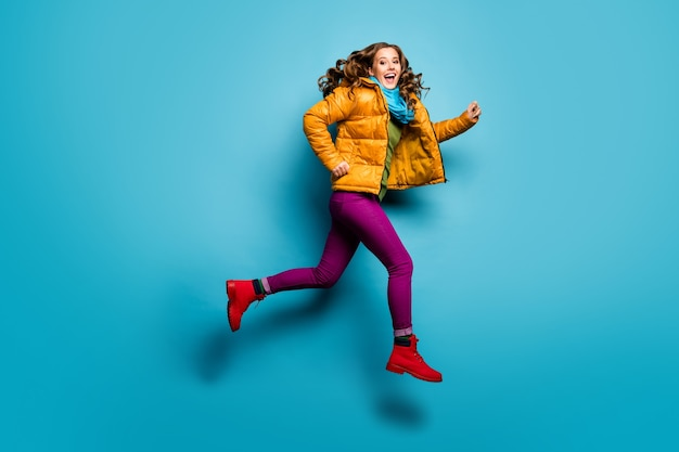 Foto de perfil de corpo inteiro de uma senhora bonita pulando alto correndo preços baixos comprando roupas casuais casaco amarelo cachecol calça magenta sapatos vermelhos parede azul isolada