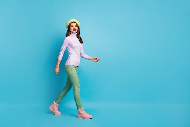 Foto de perfil de corpo inteiro de uma senhora bonita turista caminhando pela rua no exterior viajante usa boina verde roxa de gola alta e botas de calça de moletom isolado na parede azul