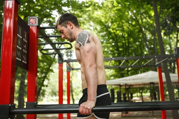 Foto de perfil de esportista fazendo mergulhos de tríceps ao ar livre