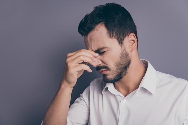Foto de perfil de jovem empresário segurando ponte nasal e dor de cabeça enxaqueca