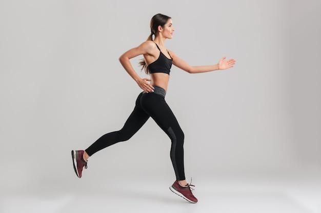 Foto de perfil de mulher branca energética no sportswear correndo, isolado ao longo da parede cinza