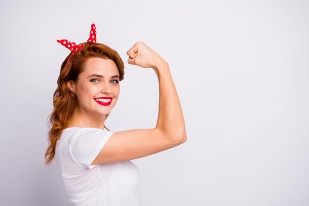 Foto de perfil de mulher encantadora positiva treinar fitness ginásio mostrar mão tríceps aproveite seu efeito de treino vista roupas bonitas isoladas sobre parede de cor branca