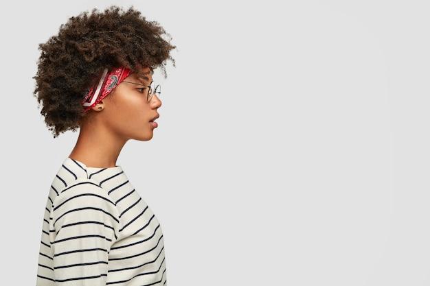 Foto de perfil de mulher negra com corte de cabelo afro, expressão pensativa