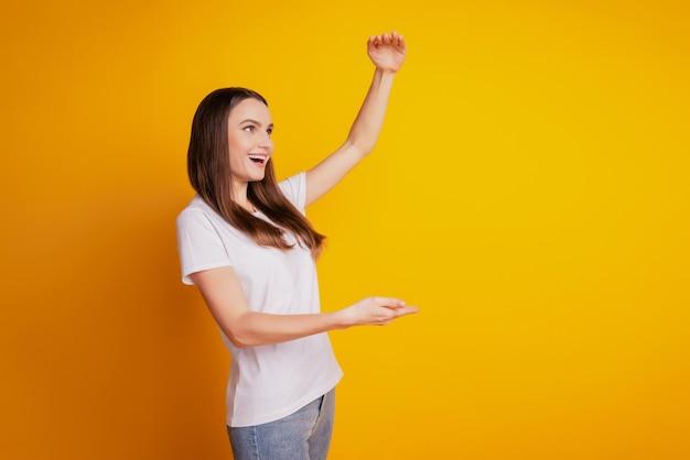 Foto de perfil de senhora com mãos segurando um grande espaço vazio e vestindo camiseta branca posando em fundo amarelo