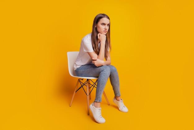 Foto de perfil de senhora sentada cadeira mão segurar o queixo humor furioso usar camiseta branca posando em fundo amarelo