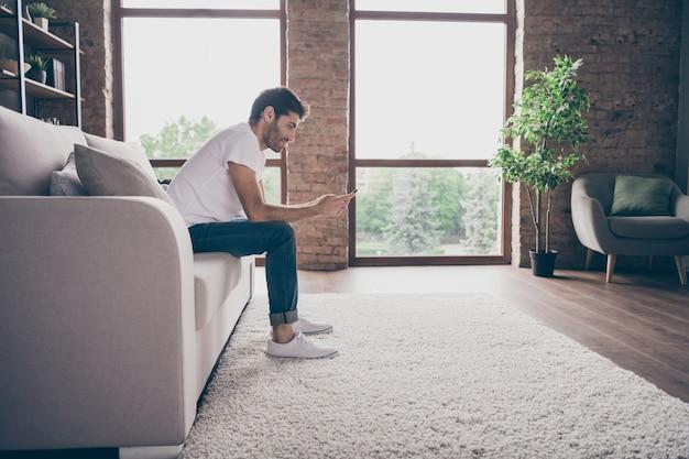 Foto de perfil de um cara mestiço sentado em um sofá confortável segurando um telefone, lendo mensagens de texto com notícias positivas com a namorada, cartas de amor, vestir roupa casual sala de estar plana