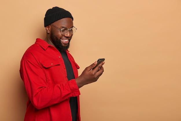 Foto de perfil de um hipster elegante de pele escura em uma camisa vermelha da moda e um chapéu preto, segura smartphone e digita e-mail