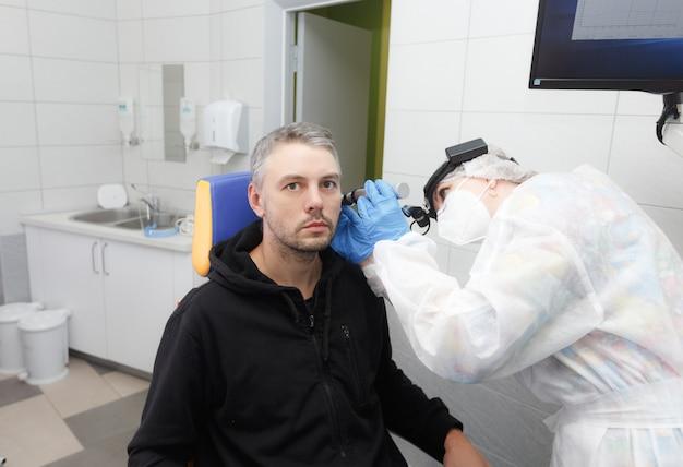 Foto de perfil de um otorrinolaringologista segurando um otoscópio na orelha do paciente, fazendo um exame.