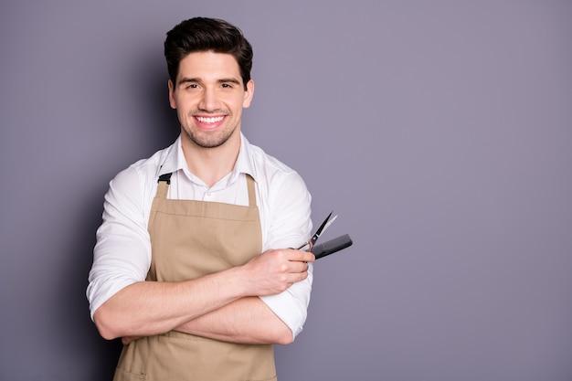 Foto de perfil de um trabalhador atraente segurar o penteado ferramentas de corte tesoura pentear cabeleireiro profissional convidando cliente sentar usar avental camisa branca isolada parede cor cinza