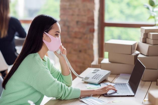 Foto de perfil de uma empresária asiática organizando máscaras médicas para gripe facial embalagens caixas de entrega falando telefone fixo detalhes do pedido do cliente anotando caderno de informações escritório doméstico dentro de casa
