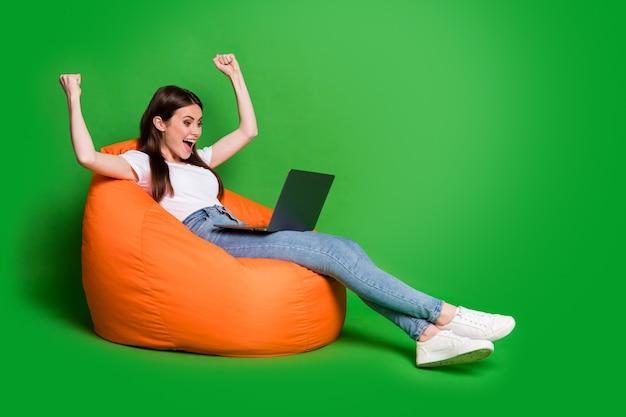 Foto de perfil de uma jovem fofa animada com os punhos erguidos segurando um vestido para laptop, pano casual, sentado em um pufe isolado no fundo verde