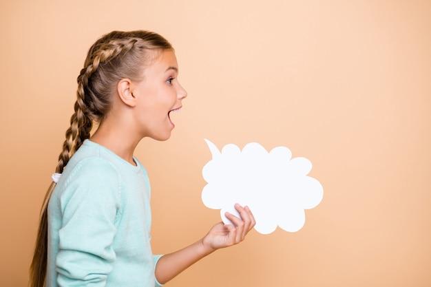 Foto de perfil de uma linda garotinha animada segurando uma nuvem de papel vazia gritando em voz alta, expressando ideias, pensamentos, vestindo uma blusa azul isolada na parede bege