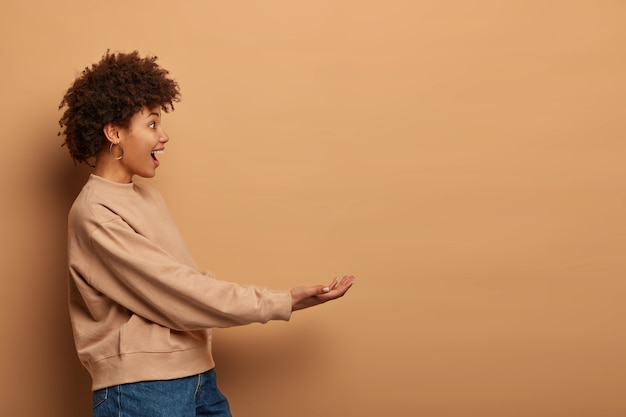Foto de perfil de uma mulher afro-americana feliz e cacheada fingindo que está segurando algo, mantém as mãos estendidas, usa um macacão marrom e jeans e está encostado na parede bege
