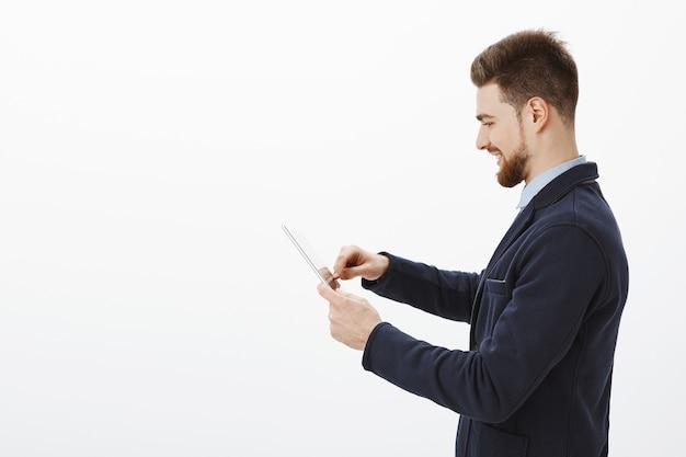 Foto de perfil do empresário elegante, confiante e bem-sucedido, com barba e penteado incrível em um terno elegante usando tablet digital sorrindo encantado, verificando a renda da empresa