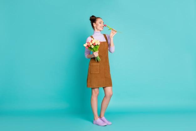 Foto de perfil em tamanho real de doce sonhadora encantadora romântica namorada segurar cheiro buquê florescendo presente fechar olhos usar sapatos violetas suéter marrom vestido curto isolado azul-petróleo cor de fundo