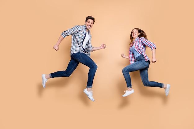 Foto de perfil em tamanho real de duas pessoas malucas pulando alto em frente apressado em lojas femininas masculinas, comprando roupas casuais, isolado fundo bege