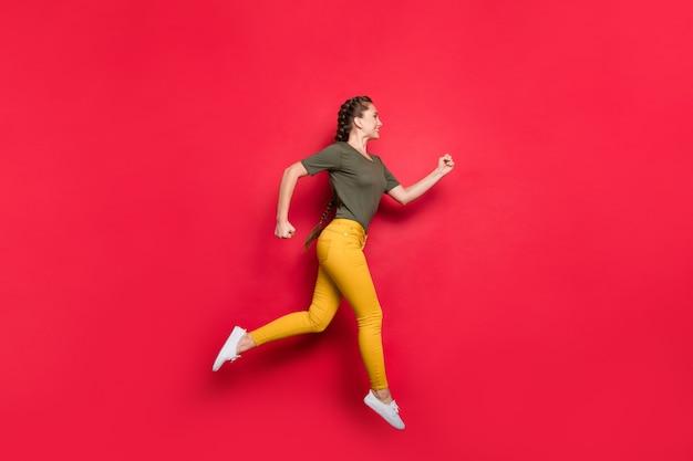 Foto de perfil em tamanho real de senhora milenar pulando competições de esportes de alta velocidade participante da maratona em velocidade de corrida vestir calças amarelas casuais camiseta verde isolado fundo de cor vermelha