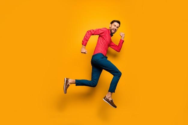 Foto de perfil em tamanho real de um cara engraçado pulando alto em um shopping center preto sexta-feira usando uma camisa vermelha na moda e calça de gravata borboleta.