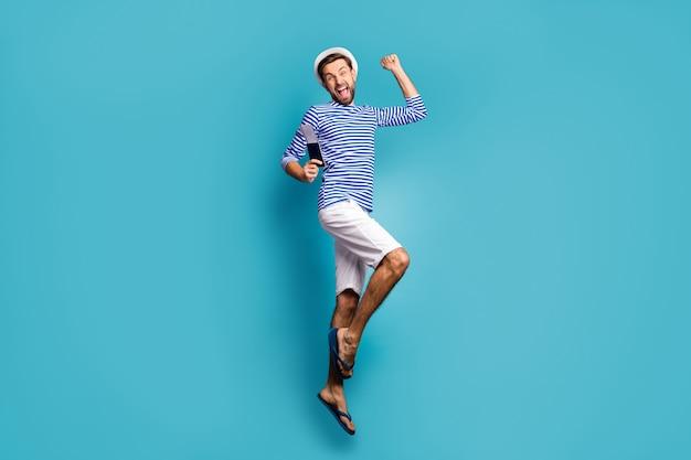 Foto de perfil em tamanho real de um cara maluco funky, um turista, pula alto, comemore o início das férias, finalmente consegui visto usar camiseta listrada de marinheiro.