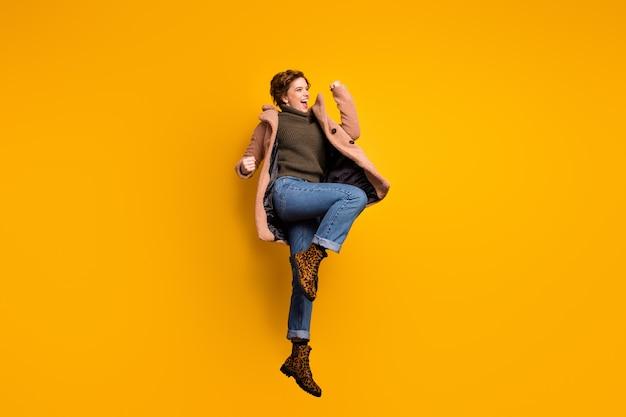 Foto de perfil em tamanho real de uma linda senhora descolada pula alto espantada férias comece a usar casaco casual rosa pulôver calça jeans leopardo