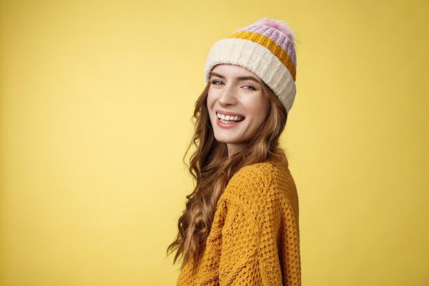 Foto de perfil encantadora garota feliz e sorridente, despreocupada, girando a câmera sorrindo com alegria, aproveitando as férias de inverno, se divertindo esquiando, em pé, divertindo-se, rindo, vestindo um chapéu de malha suéter de fundo amarelo