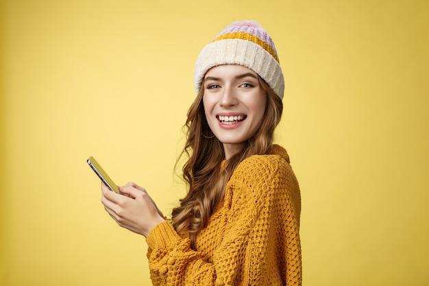 Foto de perfil entretido jovem encantadora jogando telefone celular segurando um smartphone girando a câmera ...