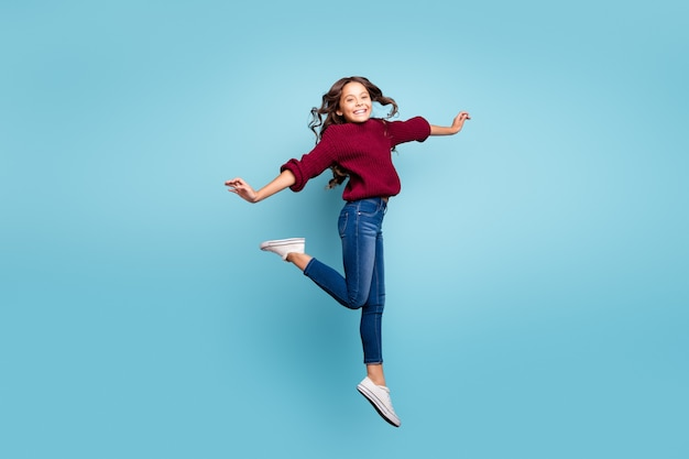 Foto de perfil lateral de corpo inteiro de corpo inteiro de alegre positivo sorridente e sorridente menina radiante dançando como bailarina encaracolado ondulado pulando isolado fundo de cor azul vívido