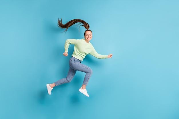 Foto de perfil lateral de corpo inteiro de corpo inteiro de corredor engraçado feminino pulando com rabo de cavalo de cabelo comprido isolado em fundo de cor azul brilhante
